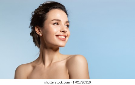 Toothy smiling young woman with shiny glowing perfect facial skin and bare shoulder looking aside beauty studio portrait on blue copy space. Cosmetology, dermatology. Dental and skin treatment