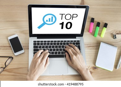 Top 10 list website on the screen of laptop computer with hands typing on keyboard