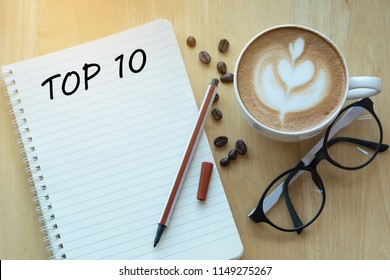 Top 10 word on notebook with glasses, pencil and coffee cup on wooden table. Business, internet, education, technology concept.
