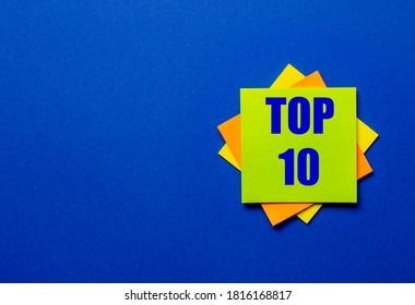 TOP 10 is written on bright stickers on a blue background. Copy space