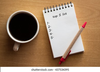 Top 5 list written on notebook, wooden background with a cup of coffee.