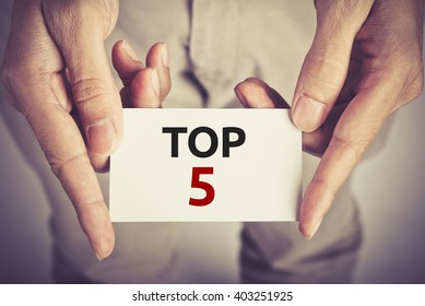 """"""" TOP 5 """" word on card hold by man"""