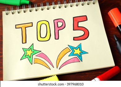 TOP 5 written on a notebook on a wooden background.