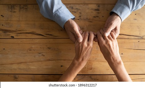 Top above close up view compassionate middle aged man holding wrinkled hands of elderly woman, copy space. Loving old mature married retired couple showing care, supportive family relations concept.