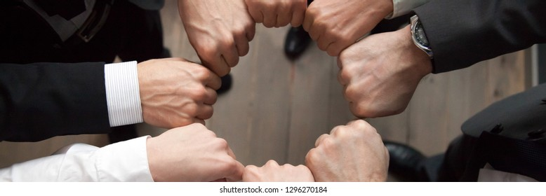 Top above close up view group of businessmen in formal suits standing putting hands fists in circle shape. Teamwork trust motivation support concept, horizontal photo banner for website header design