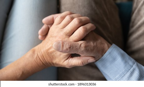 Top above close up view loving affectionate old senior married family couple holding hands, enjoying sweet tender moment together at home, showing support and care to each other, relations concept.