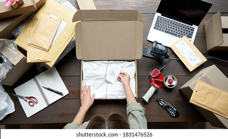Top above closeup view of female online store small business owner entrepreneur packing package post shipping box preparing delivery parcel on table. Ecommerce dropshipping shipment service concept.