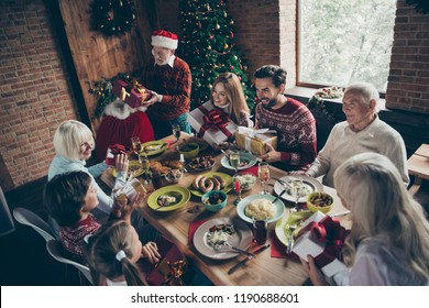 Top above high angle view of noel gathering, meeting. Adorable large  grandparent in headwear giving away, changing gifts sister brother son daughter at feast lunch table fun joy bag sack