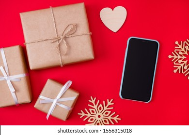 Top above high angle view photo of telephone flakes of snow and wrapped presents lying on red bright color background with heart shaped postcard