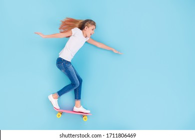 Top above high angle view full length photo of energetic excited kid girl ride skateboard empty space enjoy fun lay isolated over blue color background