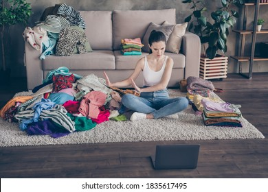 Top above high angle view photo of serious girl understand her shopaholic problem, sit floor carpet legs crossed use laptop refuse buy clothes reject big messy pile in house indoors