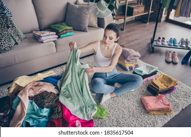 Top above high angle view photo of focused volunteer girl sit floor, carpet arrange her used clothes decide what she will give charity in house indoors