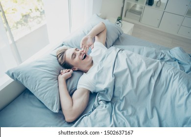 Top above high photo of positive cheerful brown haired man awake from healthy sleep yawn feel satisfied after night dreams in room house indoors