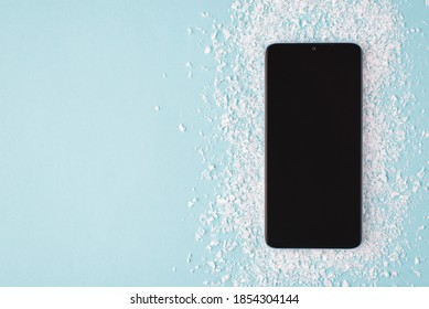 Top above overhead view layout photo of black smartphone on snow isolated on blue background with copyspace