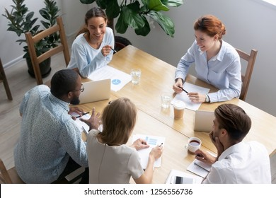 Top above view diverse multiracial businesswomen and businessmen sitting in conference room during seminar. Young positive company staff negotiating at briefing share ideas and reviewing sales stats