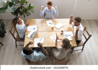 Top above view happy multi-ethnic coworkers scream, applaud and clench fists celebrating win and success. Great business achievement, good news, attainment of common aim, unbelievable project results