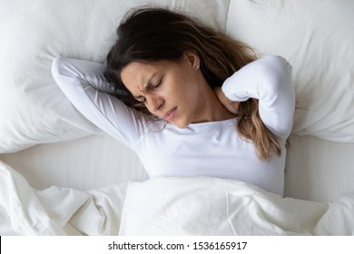 Top above view head shot close up stressed young mixed race woman feeling neck ache, suffering from painful feeling in neck in morning after sleeping on uncomfortable pillow at home or hotel room.