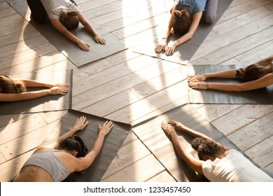Top above view yoga position Child Pose performed by six diverse young slim yogi females get settled in circle wearing sportswear indoor in the morning. Group training healthy active lifestyle concept
