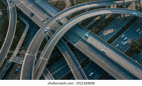 Top up aerial drone view of elevated road and traffic junctions in Chinese metropolis city Chengdu during sunny day. Modern construction design of traffic ways to avoid traffic jams. Few vehicles.