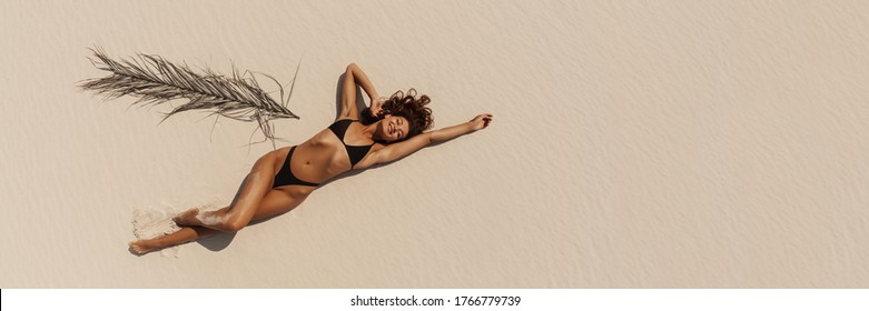 Top Aerial Drone View of Woman in Swimsuit Bikini Relaxing and Sunbathing on Beach