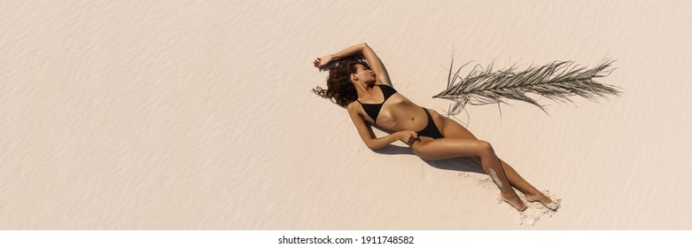 Top aerial drone view of woman in swimsuit relaxing and sunbathing on beach Near The Ocean. Attractive brunette girl in black bikini laying on a sandy coast with palm leaf. Gorgeous tanned mixed race