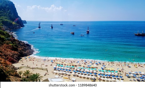 Top aerial view from above of paradise beach resort in Alanya, Turkey, with gold sand, azure blue water of Mediterranean sea with ships, palms, rows of chaise lounges with colorful sun umbrellas