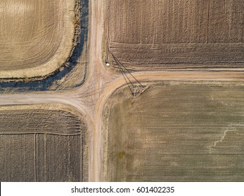 Top Aerial view of crossroad and furrows row pattern in a plowed field prepared for planting crops in spring. Growing wheat crop in springtime. Aerial view of harvest fields in Lithuania