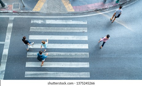 Top aerial view crosswalk with people walk across road with signage. Concept Pedestrians passing a crosswalk. Rush hour in the city