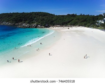Top aerial view from drone of tropical island with white sandy beach, blue transparent water and coral reefs. There are some people swimming and relaxing on the beach. Thailand.