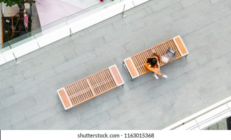 top aerial view fashion woman with shopping bag uses smartphone sit on wooden bench at walkway pedestrian with blur people are walking, , concept of social still life with technology and lifestyle