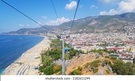 Top aerial view from funicular cableway of Cleopatra beach resort in Alanya, Turkey, with sand, blue water of Mediterranean sea with ships, palms, rows of chaise lounges with colorful sun umbrellas