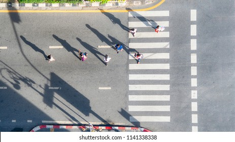 Top aerial view of group people walk at street city with pedestrian crosswalk in transport traffic road with sunlight and shadow silhouette