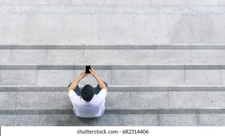 the top aerial view of the man in white shirt uses mobile phone and sits on the pedestrian concrete walk way at stair public.