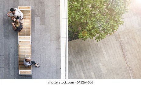 top aerial view of people sit on wood bench at the upper floor pedestrian with the lower floor of tree garden and street.