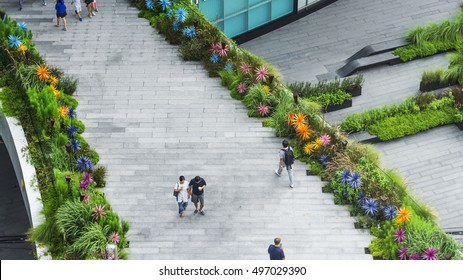 top aerial view people are walking on the bridge pedestrian and landscape green area garden walkway in the business city area.
