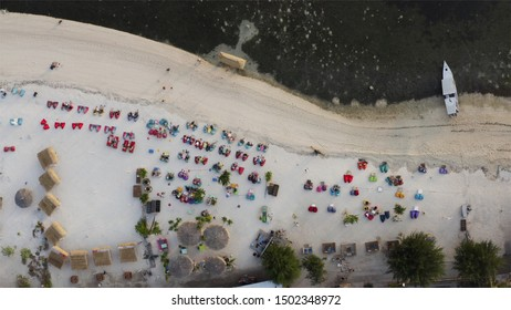 Top aerial view of sandy beach, boat in ocean at low tide, straw umbrellas and roofs at resort, tourists enjoy the evening in armchairs. GILI AIR Air island, Indonesia