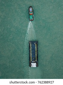 Top aerial view of a tug boat towing an empty barge taken on a drone
