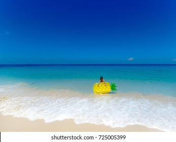 Top aerial view of a woman with inflatable mattress in a pineapple shape going to swim. On holidays having fun and relaxing at the beach.