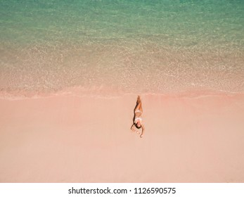 Top aerial view of a woman on the beach in a bikini lying and sunbathing on pink beach. Pink Beach, Padar Island, Komodo Flores, Indonesia
