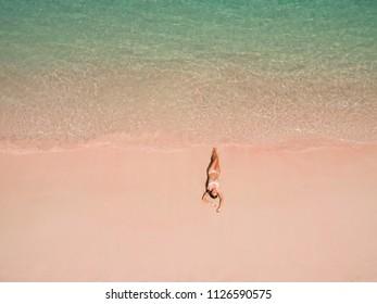 Top aerial view of a woman on the beach in a bikini lying and sunbathing on pink beach. Pink Beach, Padar Island, Komodo Flores, Indonesia