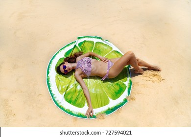 Top aerial view of a woman on the beach in a bikini lying and sunbathing on a round beach towel in the shape of lime or lemon. Photo from drone.