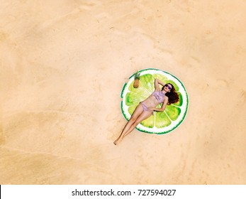 Top aerial view of a woman on the beach in a bikini lying and sunbathing on a round beach towel looks like lime or lemon. Photo from drone.