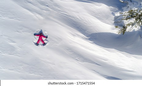 Top aerial view of young happy smiling girl making by arms snow angel figure and lying in snow, winter outdoor activity concept. Girl in the snow angel shows . Winter angel in a bright ski suit