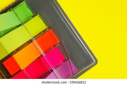 Top angle of colorful self stick notes in a black case against a yellow background