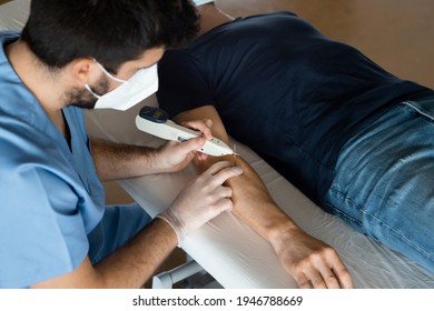 Top angle of man lying down on a stretcher of a health center, receiving a alternative treatment, Electroacupuncture dry with needle for arm injury with electric shock device, done by physiotherapist.