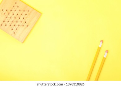 Top angle view of a pair of pencils with a wooden board of indoor games, signifying that there needs a balance between study.work and play.