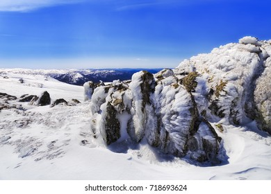 Top of Back Perisher mountain with ice covered mossy boulders on a sunny cold winter day. Snowy mountains skiing resort of Australia.