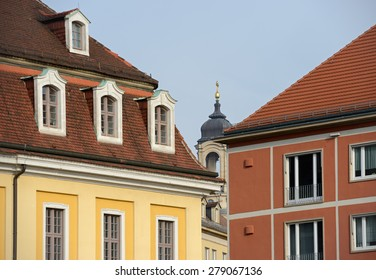 Top of bell tower of Frauenkirche church in narrow gap between bright buildings around parking on the corner of Kreuz and Ring Street at Rathaus Square in Dresden, Saxony, Germany.