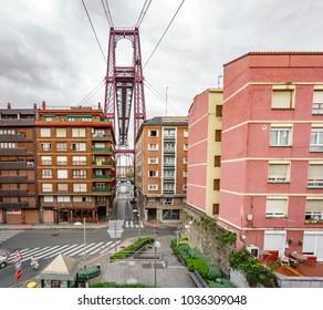 Top of the Bizkaia suspension bridge behind residential buildings in Portugalete