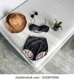 Top of black swim suit 2 peach with wide -shoulder hat , plant on pot and sunglasses on white sofa in flat lay of accessory beach concept.